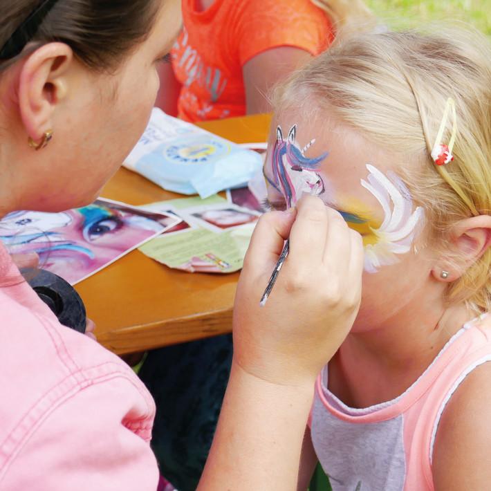 Kinderschminken Mädchen wird zum Einhorn geschminkt